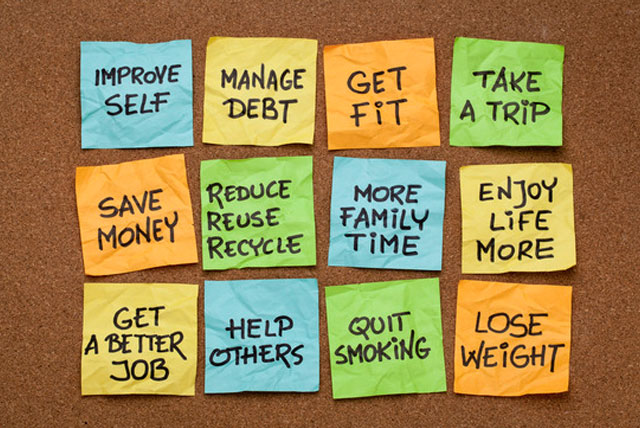 New Years resolutions hand written in marker on color sticky notes, and arranged on a bulletin board in a college dorm room.