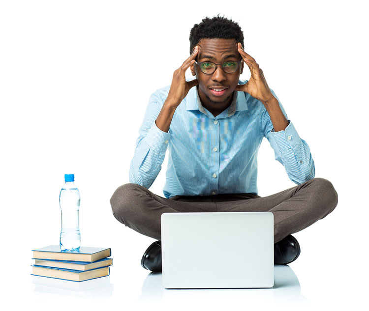 An African American college senior in stressed about a failed job search while on his laptop sitting with books and bottle of water.