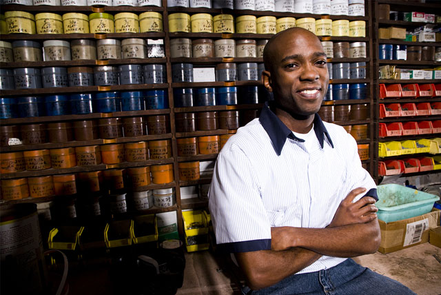 Young Black Entrepreneur sitting in front of colored inks in his printing business.