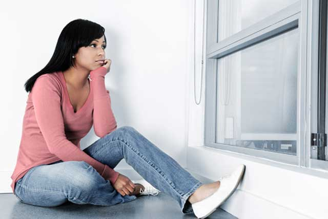 Depressed recent college graduate sitting on floor looking out of the window.