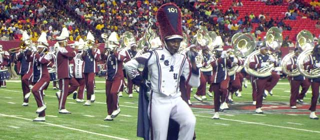 A drum major from South Carolina State University's Marching 101 leads the horn section in high stepping formation.