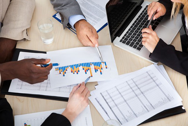 How to Become an Actuary: Image of a group of actuaries discussing risk report in a team meeting.