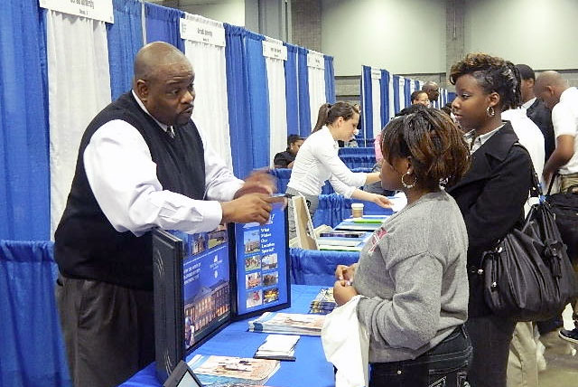 College recruiter speaks with high school students about college options at National College Fair.