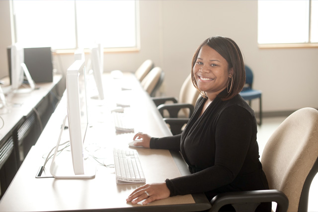 Visiting Harvard Fellow Allissa Richardson sits at computer in Journalism lab.