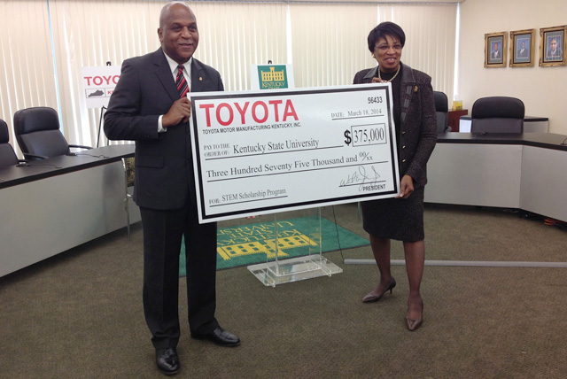 Toyota Motor Manufacturing Kentucky President Wil James (left) presents Dr. Mary Sias, president of Kentucky State University, with a $375,000 check to establish the Toyota Engineering Scholarship on March 18, 2014.
