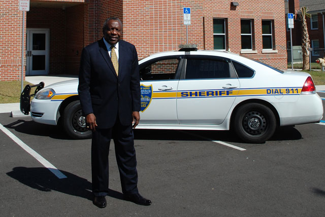 Edward Waters College President and alumnus Nathaniel Glover stands in front of a police car outside of the newly opened EWC Center for Criminal Justice and Forensic Science Facility.