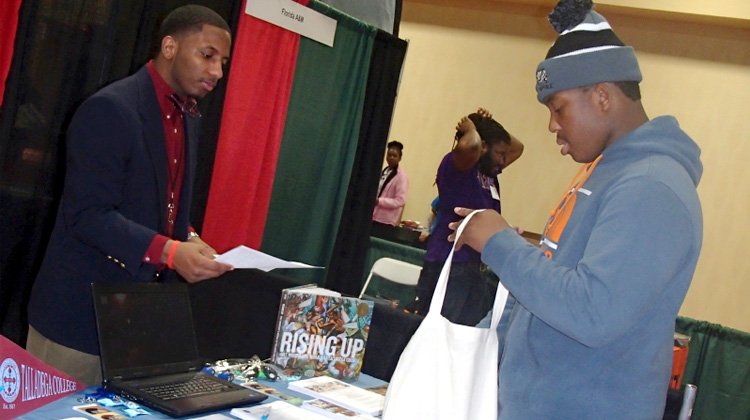 A Talladega College recruiter hands a prospective high school student some college information at the Black College Expo in Oakland, CA.