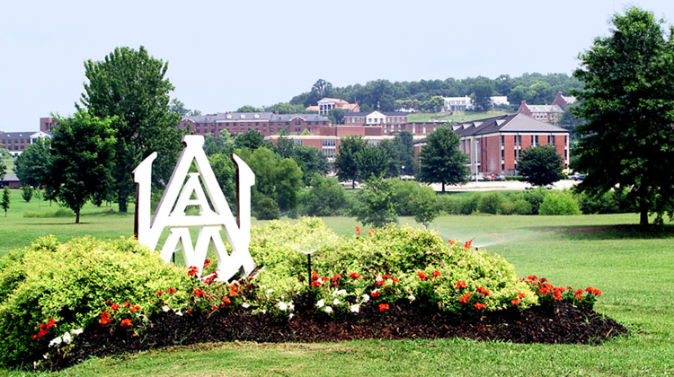 Alabama A&M University signage on a sunny day with campus in the distant background.