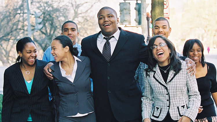 A group Ron Brown scholars and alumni walking together smiling and enjoying each other's company down a busy city street.