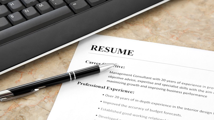 Resume on the table with laptop.