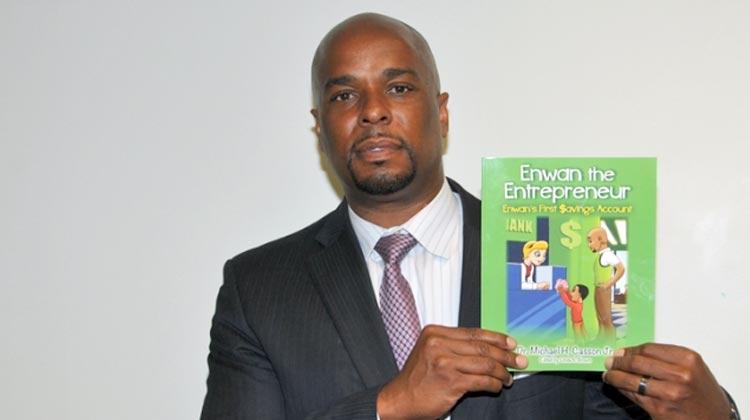 Dr. Michael A. Casson Jr., an associate professor of economics at Delaware State University holds his book Enwan the Entrepreneur – Enwan's First $avings Account.