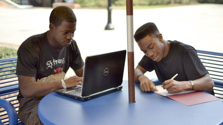 Johnson C. Smith University students on campus are working a course assignment.