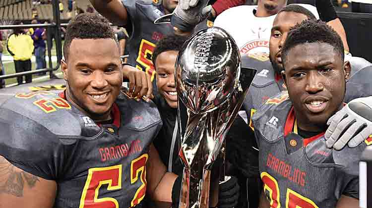 Team members from Grambling State University's Football team hold up the Bayou Classic Game Trophy.