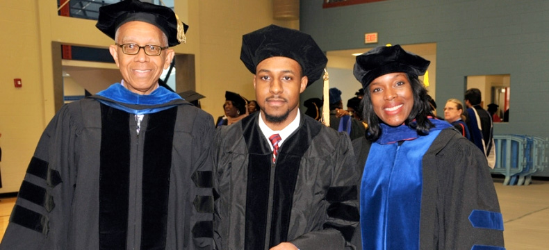 Dr. Jalaal Hayes (center) made DSU history by becoming the youngest-ever doctoral graduate at age 22.