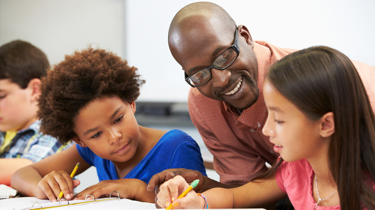 An African-American Male Teacher Helps Students Studying At Desks In Classroom.