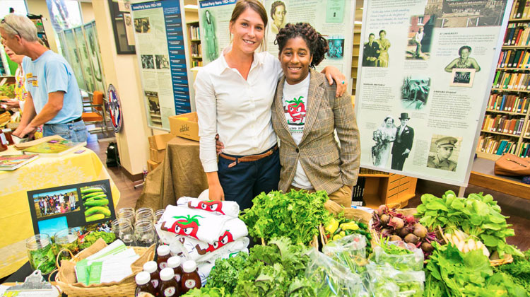Presenters at the Paul Quinn College pose in front of an organic food educational exhibit.