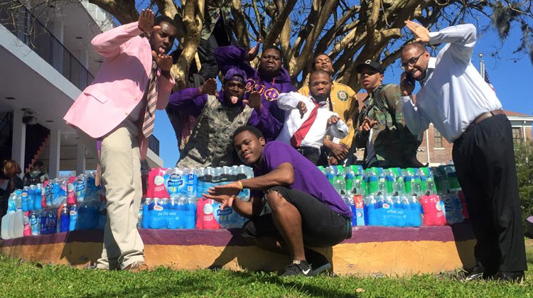 Members of the Chi Chapter of the Omega Psi Phi Fraternity, Inc. at Edward Waters College with water supllies