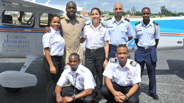Barrington Irving, an FMU alumnus and Guinness World Record holder, poises with FMU Aviation and Safety students in front of a Cessna 172 SP airplane.