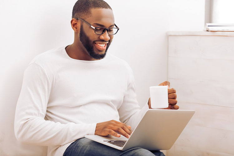 African American college student in glasses is using a laptop holding a mug and smiling while searching for apartments for rent.