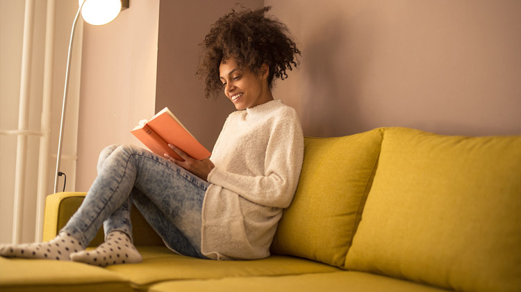 A young African American HBCU student is reading a book at home during summer break.