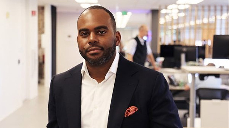 Diversity and Inclusion career veteran Damien Hooper-Campbell poses in a black sports coat inside of corporate offices.