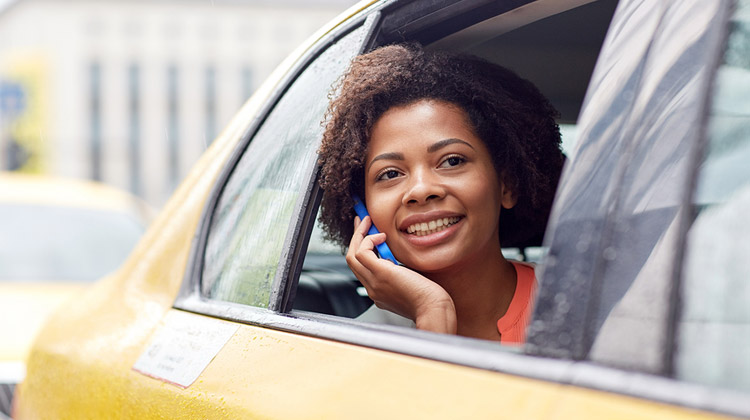 Student Travel Tips: A young smiling African American woman calling on smartphone in taxi at city street.