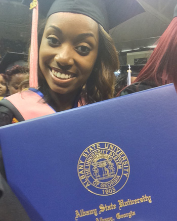 Percussionist Jazz Kelley poses with her degree during her graduation ceremony at Albany State University.