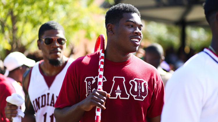 Black Greeks: A smiling member of Kappa Alpha Psi Fraternity strolls with his cane on the campus of Jackson State University during 2016 Pep Rally and yard Fest event.