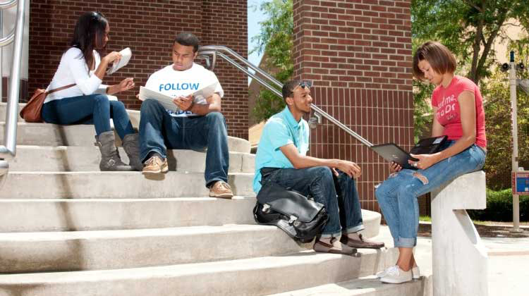 Fayetteville State University student study together on the steps outside on campus.