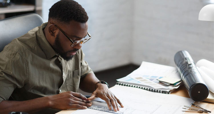 Afro-American architect working in office with blueprints