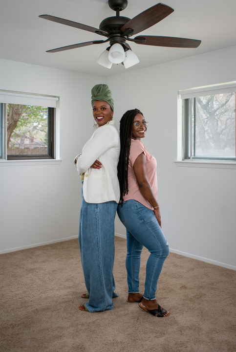 Interior designer Whitney Jones (left) stands back-to-back with Howard University graduate Brittany Goddard (right) in her empty room before a dream room makeover furnished by The Home Depot.