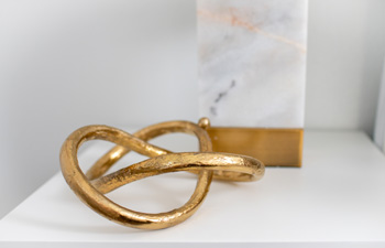 A beautiful gold eternal loop metal sculpture sits on the bedside table of Brittany Goddard's newly design dream makeover room.