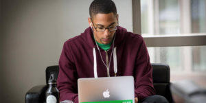 A male student applies for the HBCU CONNECT Minority Scholarship Program online while sitting in the campus library.
